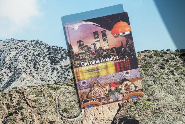 Ansicht eines Buches mit buntem Cover vor einer Berglandschaft