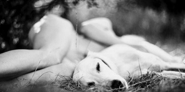 Nackte Person liegt mit Hund in der Natur.