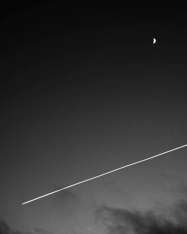 Nachthimmel mit Mondsichel und Kondensstreifen.