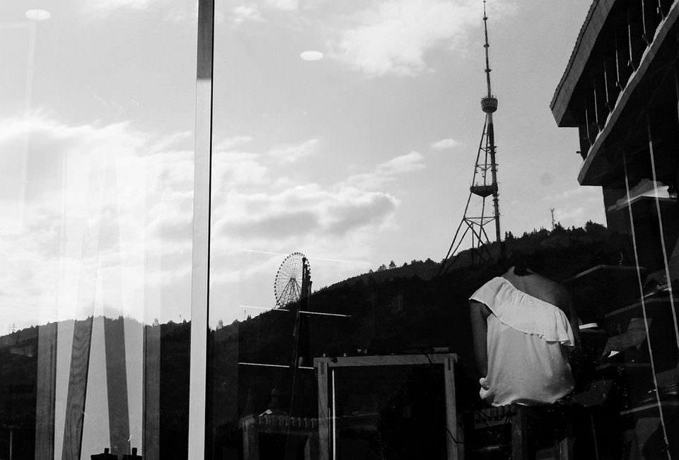 Spiegelung mit Person, Landschaft und Architektur.