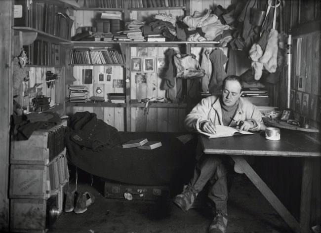 Mann schreibt an einem Tisch in einer Kammer