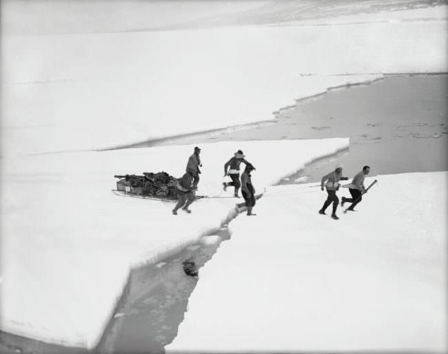 Männer überqueren mit Schlitten eine Eisscholle