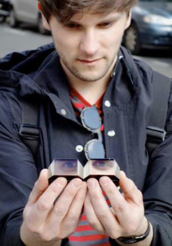 Eine Person, die in den Händen zwei Prismen hält, in denen sich Augen spiegeln.
