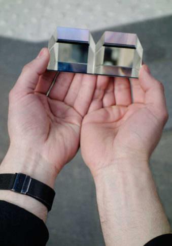 Zwei Hände, die zwei Prismen halten.