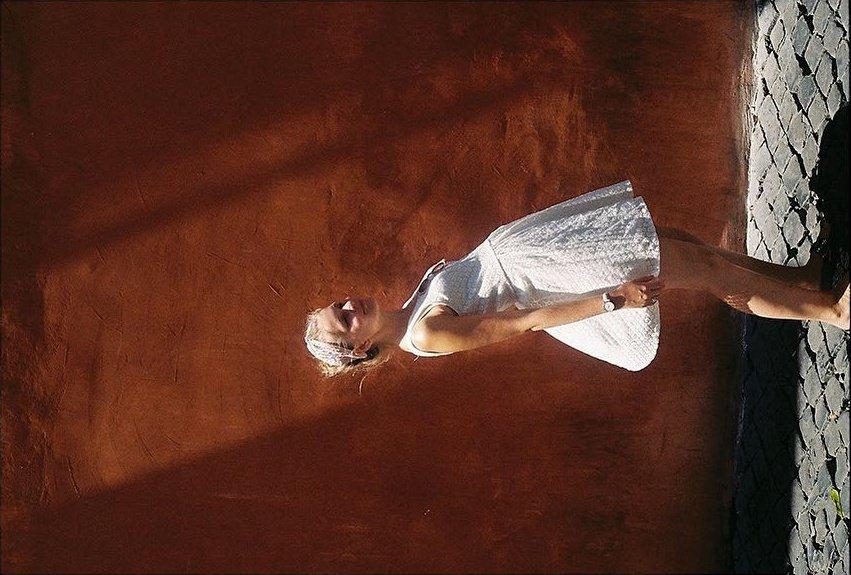Frau in weißem Kleid vor rotbrauner Fassade