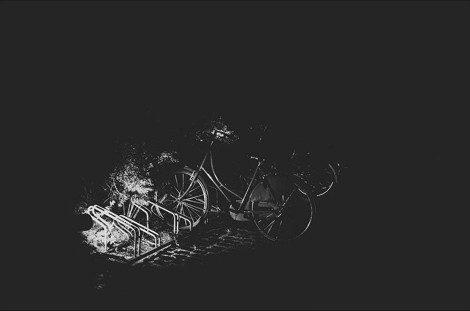 Fahrradständer mit Fahrrädern, nachts beleuchtet.