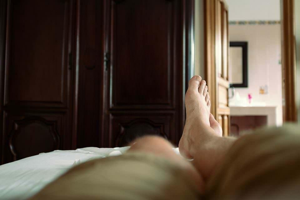 übereinandergeschlagene Beine auf einem Bett