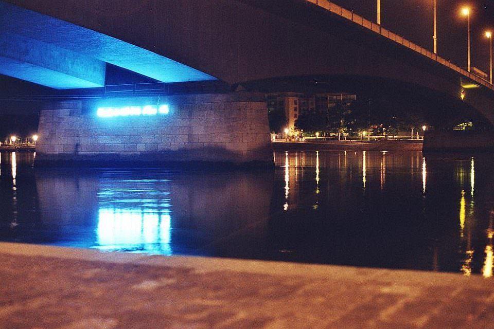 blau leuchtende Schrift unter einer Brücke in rotem Licht bei Nacht