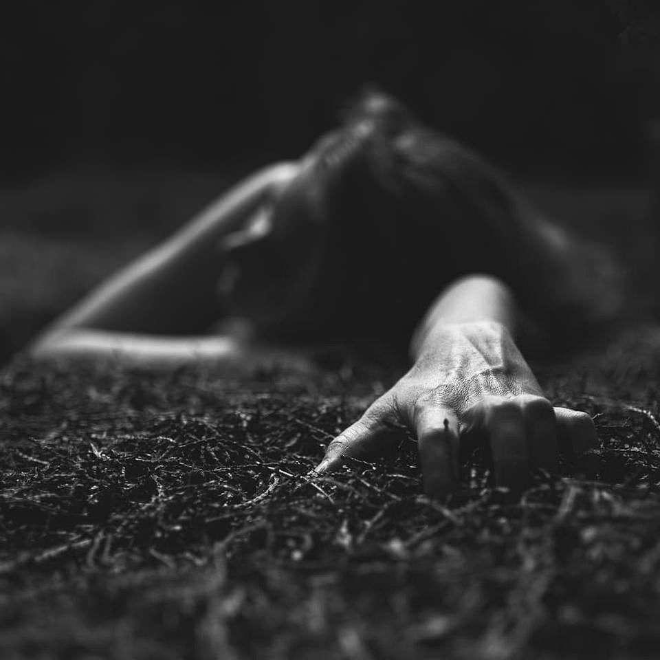 Person auf dem Waldboden, im Vordergrund ihre Hand, die sich hineinkrallt.