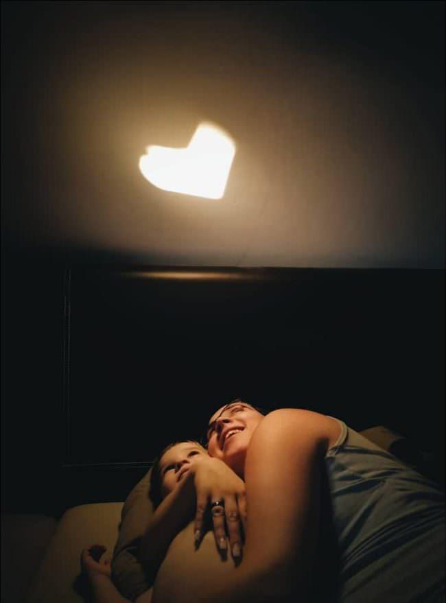 Frau mit Kind im Arm, über ihnen ein Lichtfleck in Herzform