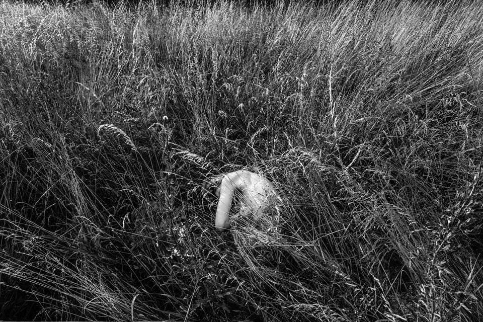 Nackte Person in hohem Gras.