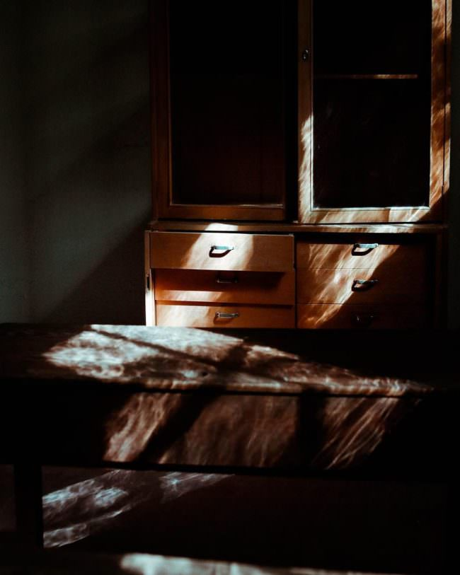 Licht fällt durch ein Fenster auf einen Holzschrank