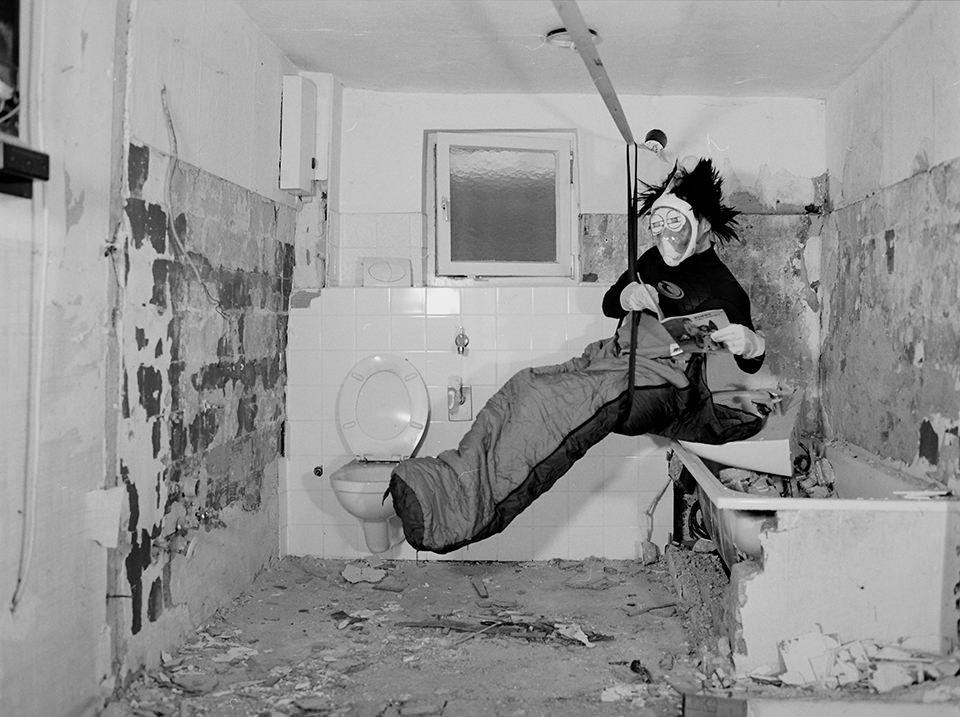 Person hängt im Schlafsack in einem alten Bad