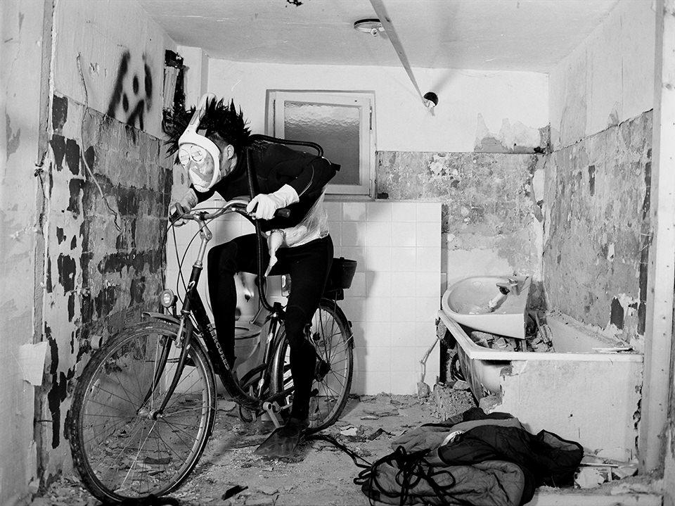 Person in einem Taucheranzug auf einem Fahrrad in einem alten Bad