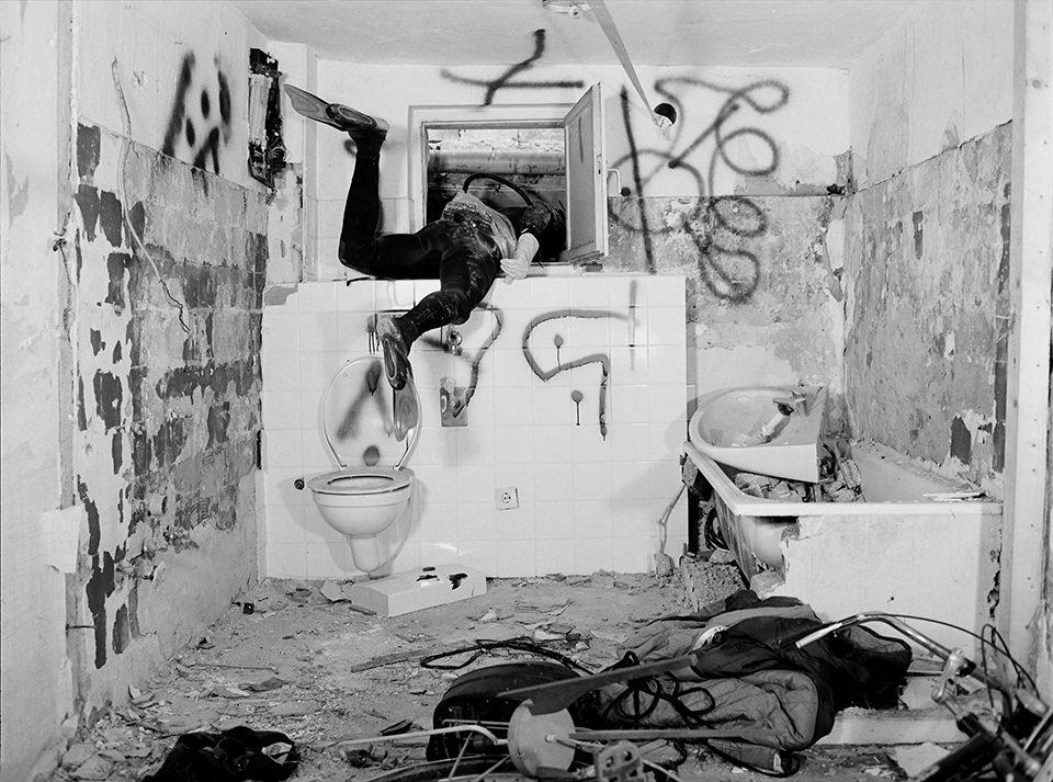 Person in einem Taucheranzugklettert aus einem alten Bad