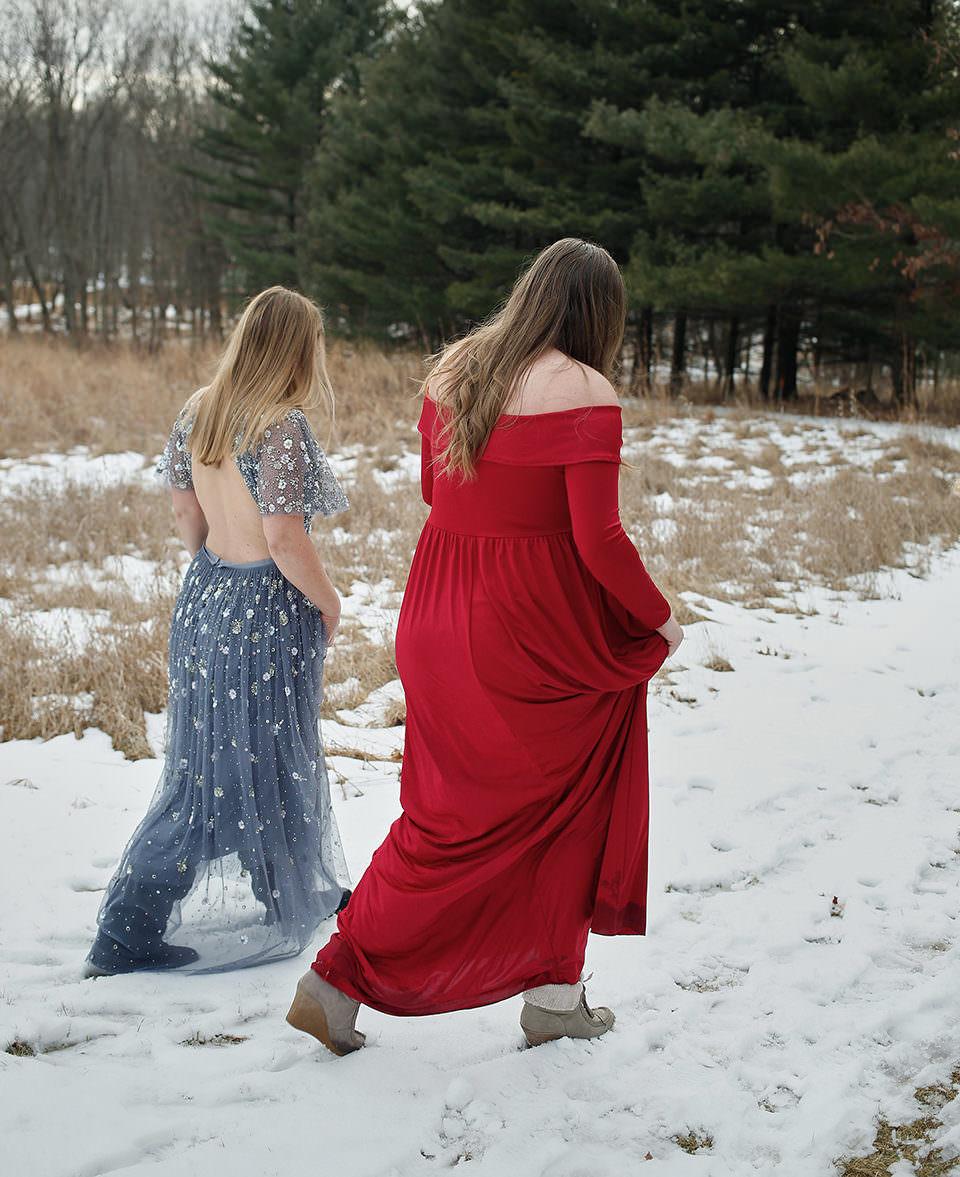 Zwei Frauen in Abendkleidern laufen durch eine Winterlandschaft