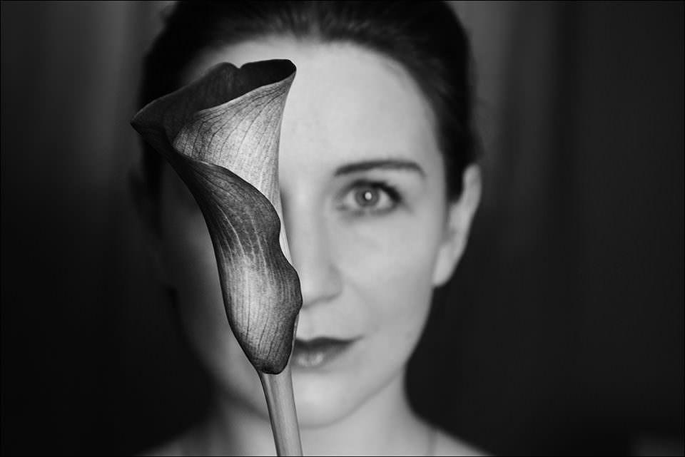 Gesicht einer Frau mit Blume davor.