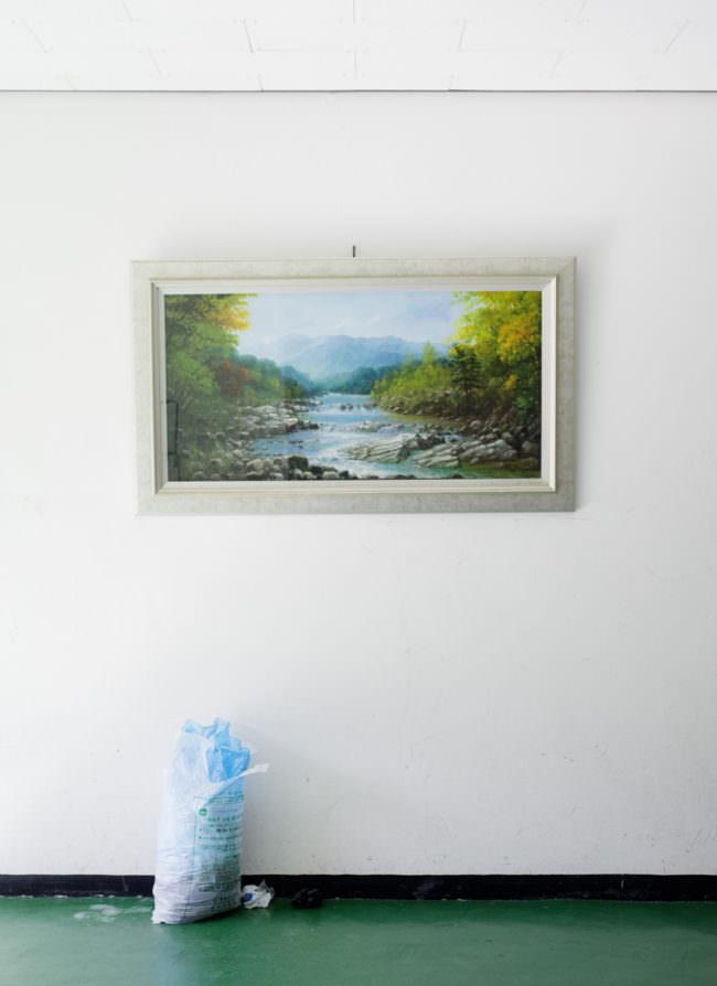 Ein gerahmtes Bild von einem Fluss hängt an einer Wand, darunter ein Müllsack.
