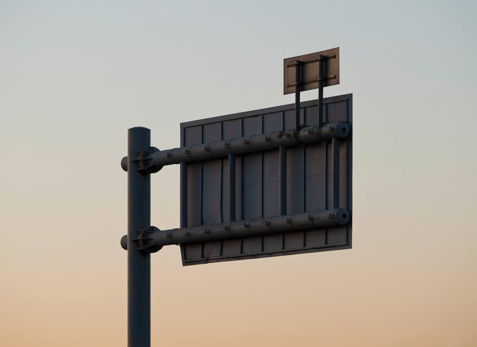 Rückseite eines Straßenschilds vor blaurotem Himmel