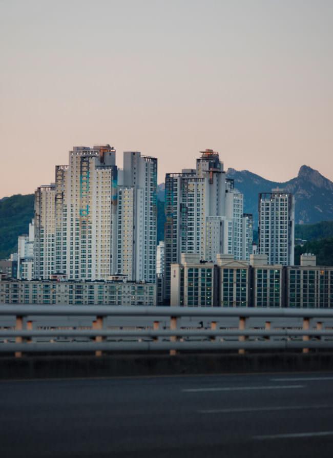Hochhäuser vor Bergen im Abendlicht