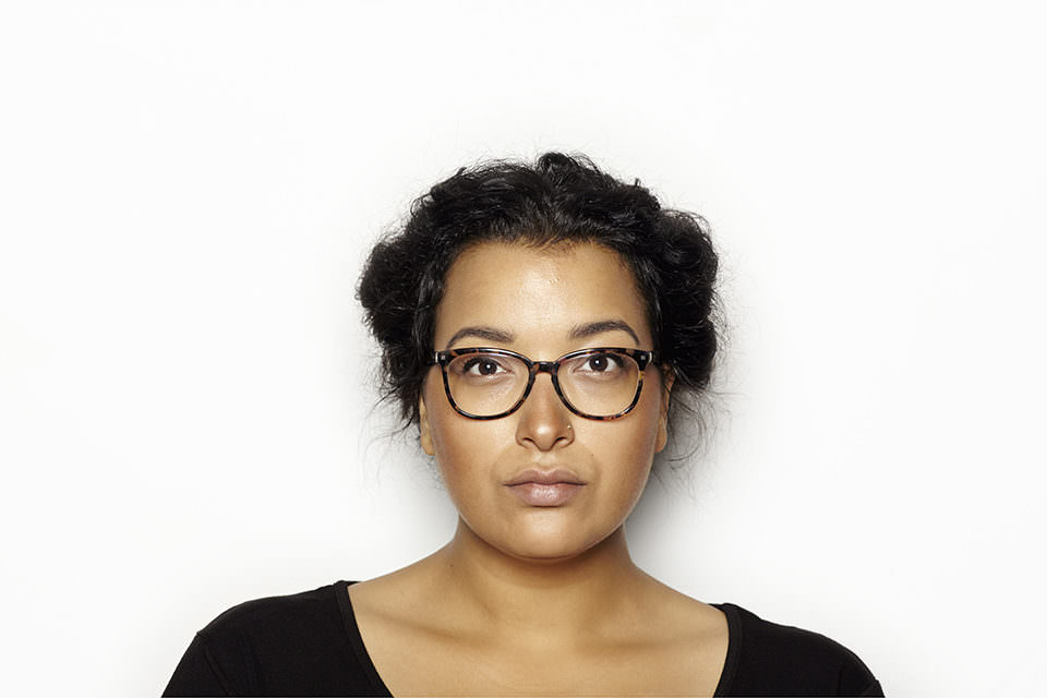 Portrait einer Frau mit dunklen Haaren und Brille.