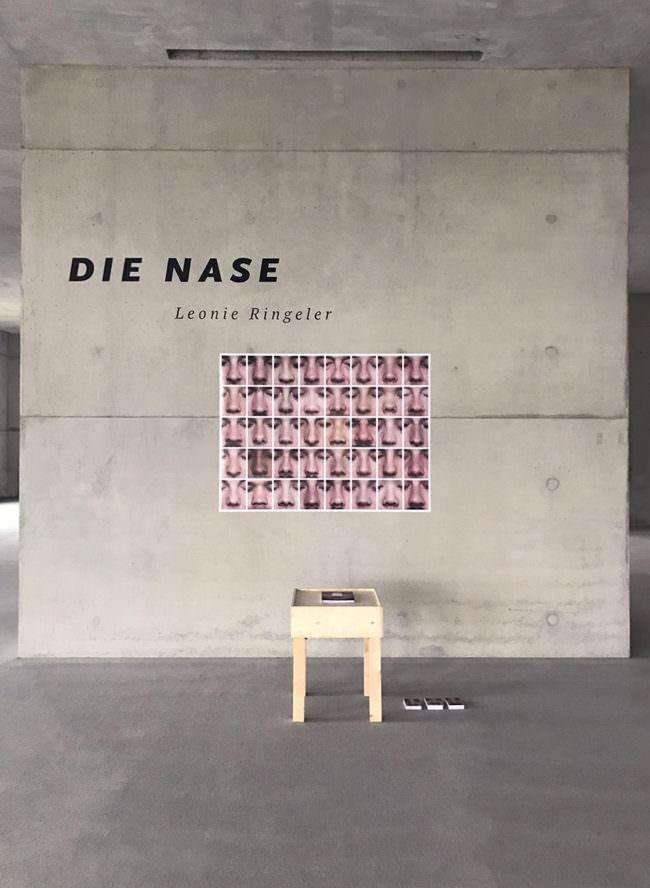 Ansicht von Wand mit Plakat voller Nasen und Tischchen.