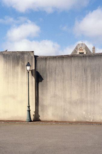 Mauer, vor der eine Straßenlaterne steht.