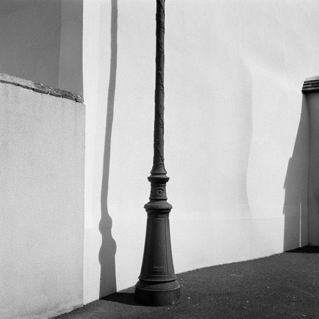 Straßenlaterne mit Schatten vor weißer Hauswand.