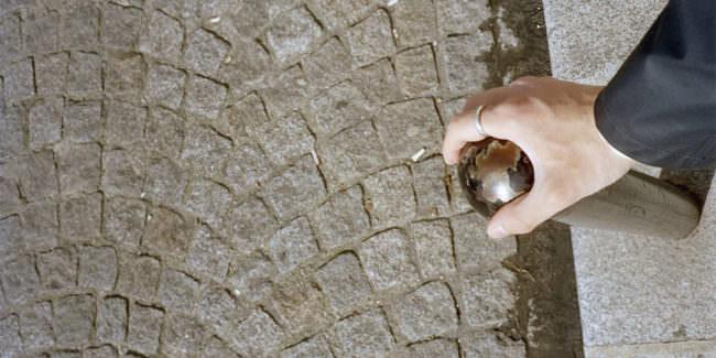 Hand auf einem glänzen Toller mit Steinweg im Hintergrund.