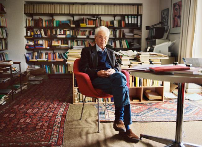 Mann vor einer Büchewand auf einem Stuhl