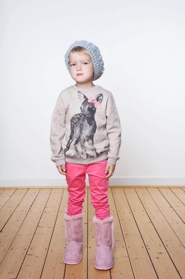 Ein Kind mit rosa Hose und Shirt mit Rehkitz stehend auf einem Holzfußboden vor einer weißen Wand.