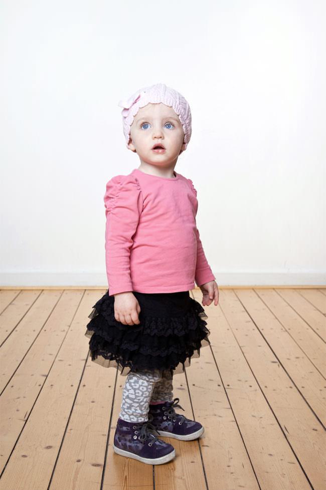 Ein Mädchen mit rosa Shirt und Tütü stehend auf einem Holzfußboden vor einer weißen Wand.