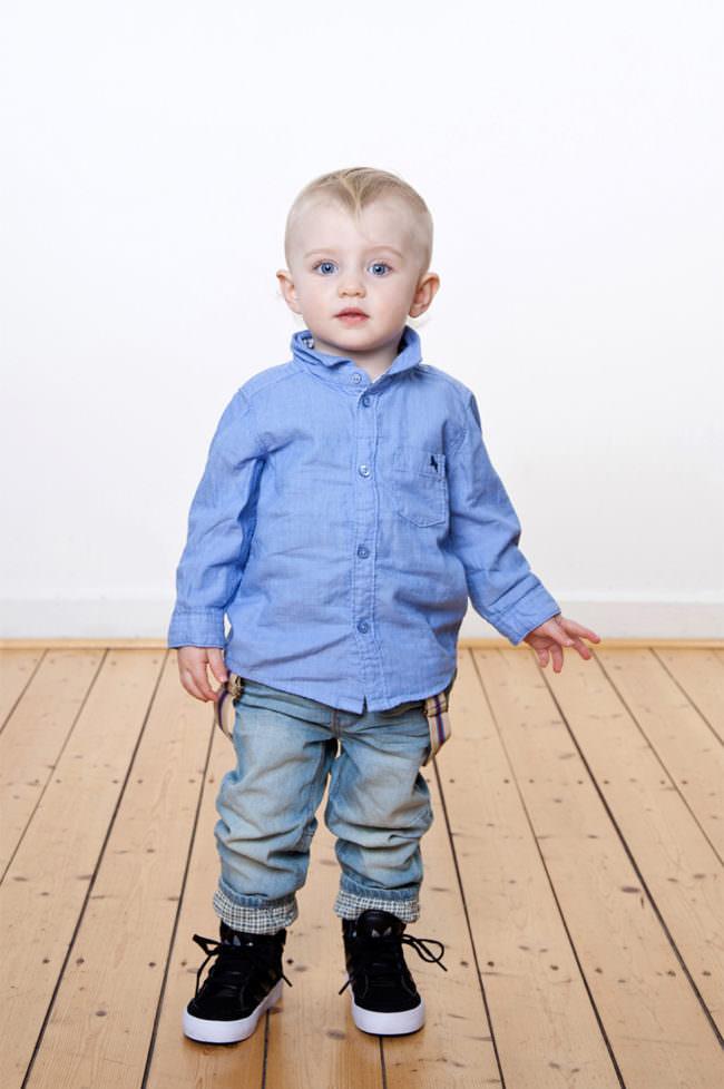 Ein Junge mit blauem Hemd stehend auf Holzfußboden vor weißer Wand.