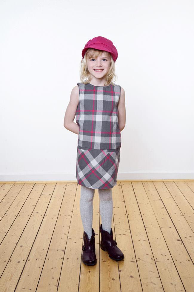 Ein Kind mit rosa gestreiftem Kleid und Mütze stehend auf einem Holzfußboden vor einer weißen Wand.