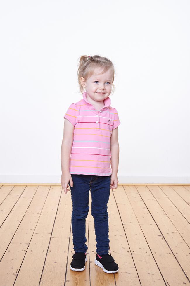 Ein Kind mit rosa Shirt stehend auf einem Holzfußboden vor einer weißen Wand.