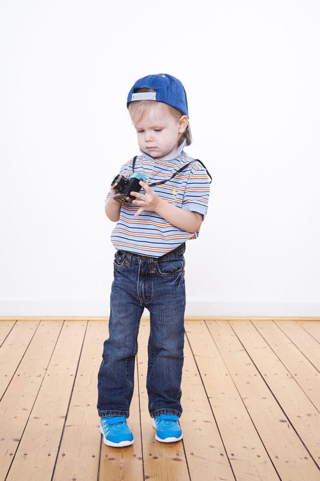 Ein Kind mit Kamera und Mütze stehend auf Holzfußboden vor weißer Wand.