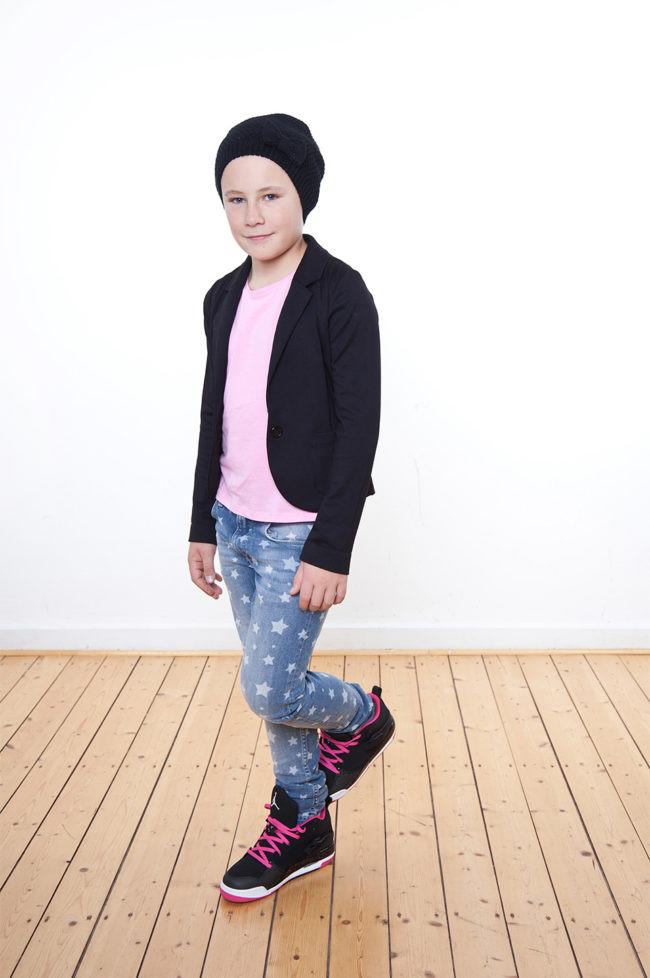 Ein Kind mit rosa Shirt und Jacke in schwarz sowie einer schwarzen Mütze, stehend auf einem Holzfußboden vor einer weißen Wand.