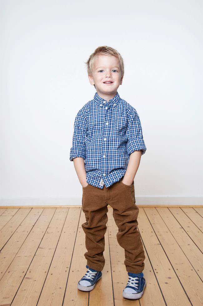 Ein Kind mit blauem Hemd stehend auf Holzfußboden vor weißer Wand.