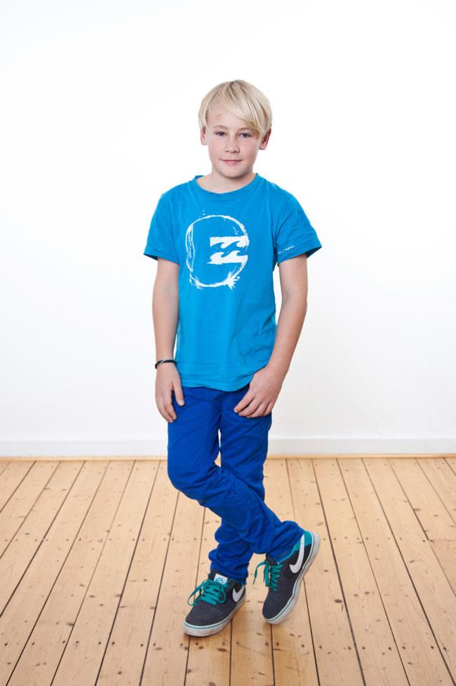 Ein Kind mit blauem Shirt stehend auf Holzfußboden vor weißer Wand.