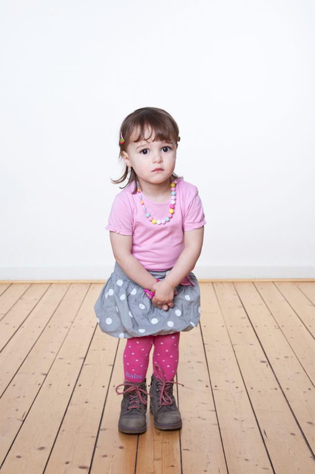 Ein Kind mit rosa Shirt und Rock stehend auf einem Holzfußboden vor einer weißen Wand.