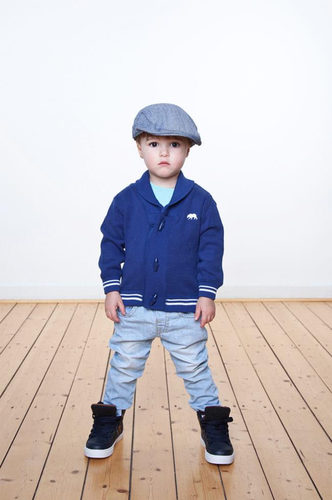 Ein Kind mit blauer Jacke und Mütze stehend auf Holzfußboden vor weißer Wand.