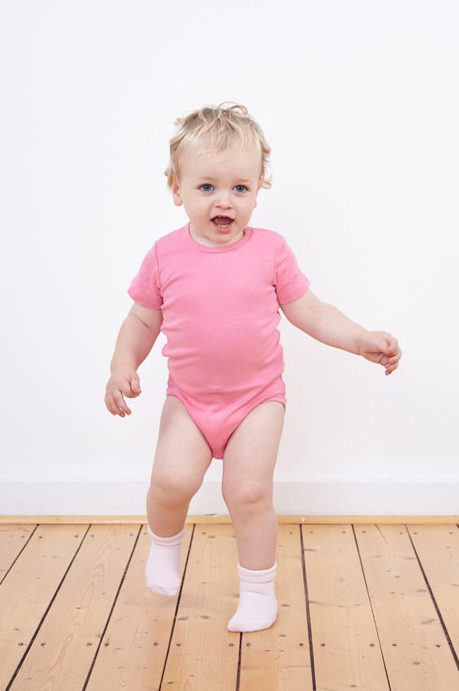 Ein Kind mit rosa Einteiler stehend auf einem Holzfußboden vor einer weißen Wand.