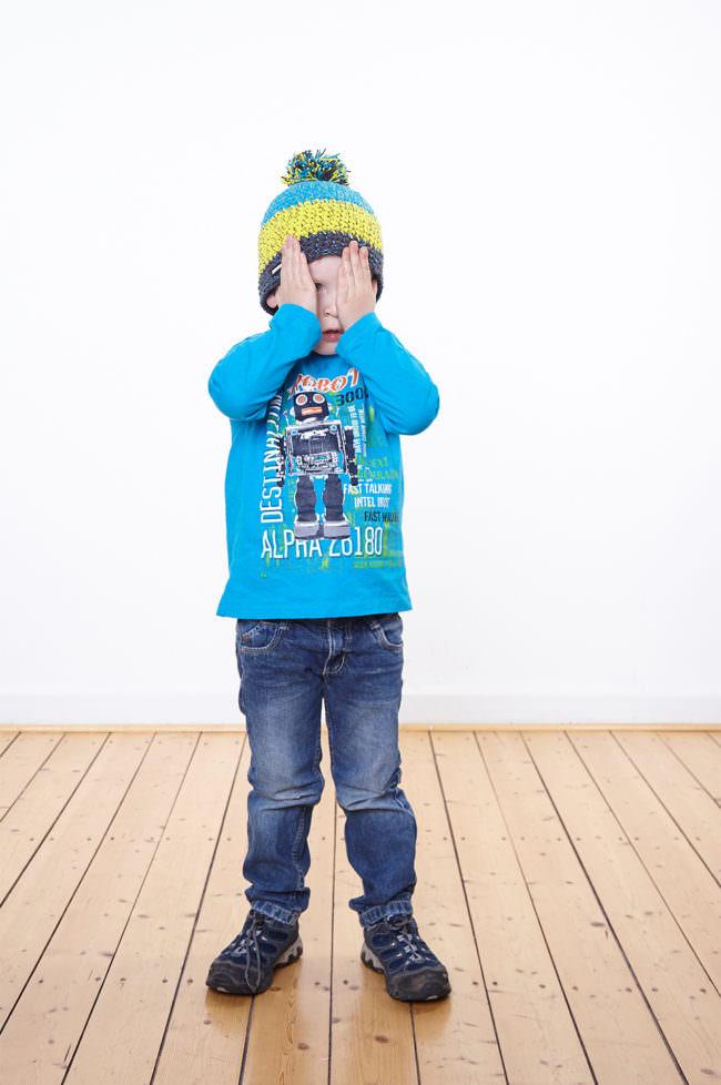 Ein Kind mit blauem Shirt stehend auf Holzfußboden vor weißer Wand. Es trägt eine Mütze und hält seine Hände vors Gesicht.