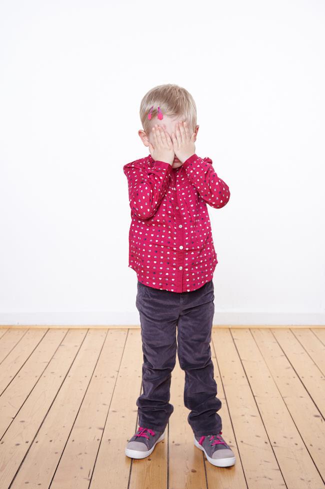 Ein Kind mit rosa Shirt stehend auf einem Holzfußboden vor einer weißen Wand, Hände vor dem Gesicht.