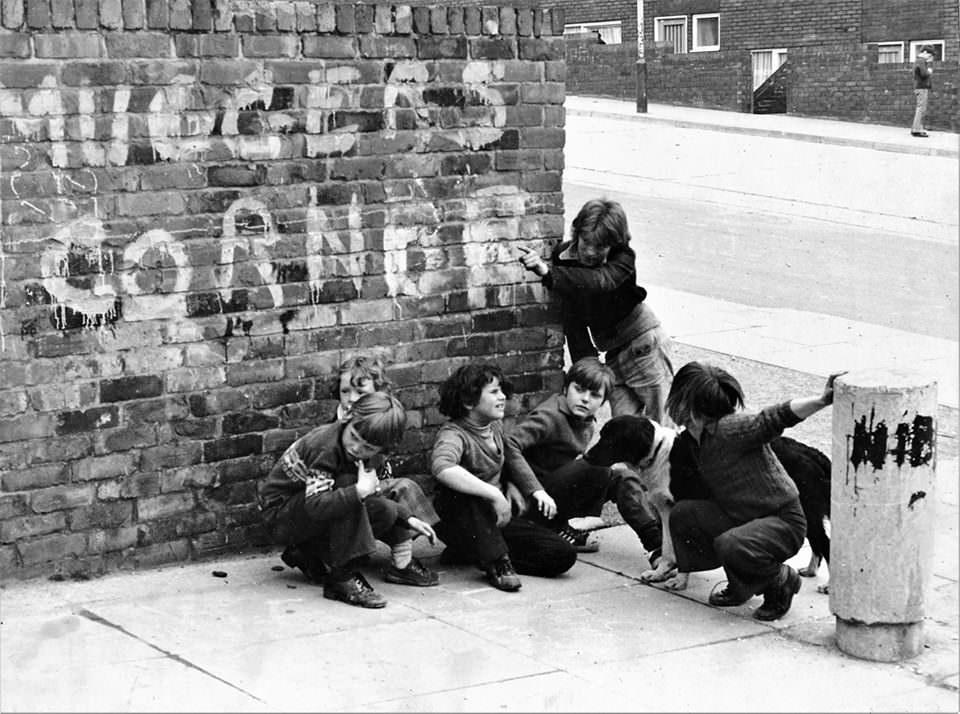 Kinder spielen an einer Hausecke