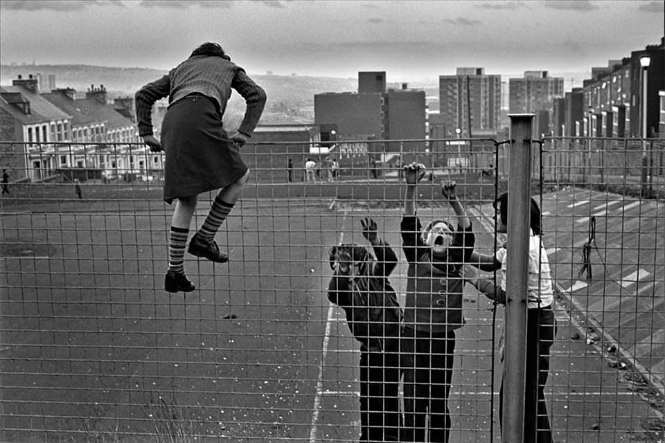 Kinder klettern über einen Zaun