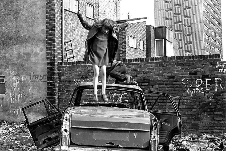 Ein Mädchen springt auf einem kaputten Auto