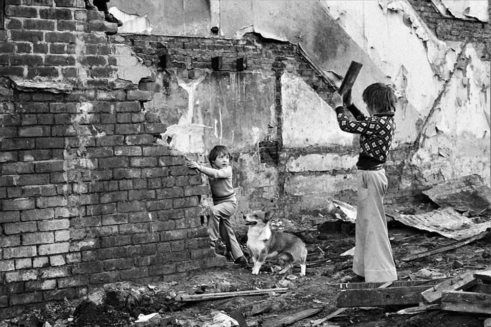 Kinder spielen an einem kaputten Haus
