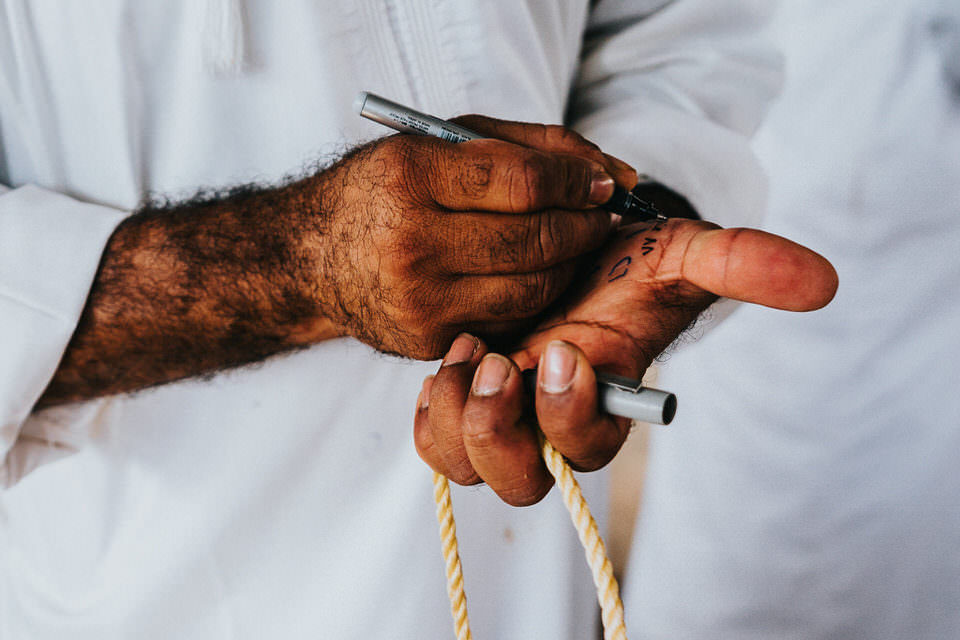 Mann schreibt sich etwas auf die Hand