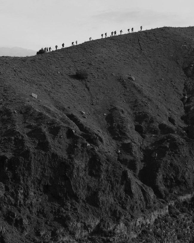 Menschenkette auf einem Hügelkamm.